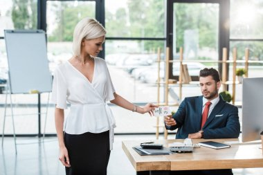 attractive blonde girl giving card with call me lettering to man in office