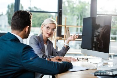 Selective focus of attractive businesswoman in glasses looking at coworker near computer monitor with blank screen stock vector