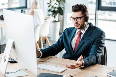 Selective focus of displeased man in glasses and headset working in office stock vector