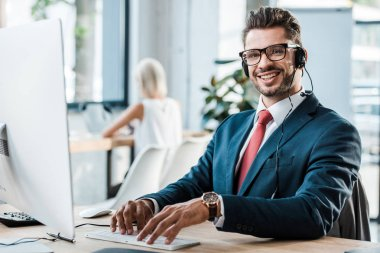 selective focus of happy operator in call canter typing on computer keyboard in office