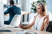 selektivní zaměření atraktivního operátora v náhlavní soupravě pracující v kanceláři