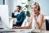 selective focus of cheerful blonde operator in headset looking at camera