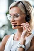 close up of cheerful blonde operator in glasses touching headset