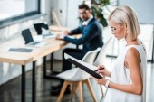 selective focus of blonde woman in glasses holding folder and documents near coworker in modern office