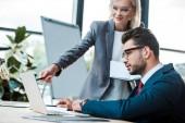 selektivní zaměření člověka na blonďatou spolupracovníka přidržením pera poblíž laptopu