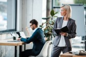 selective focus of blonde businesswoman holding notebook near coworker in office