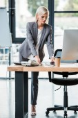 Photo attractive businesswoman in glasses and formal wear standing near table in modern office
