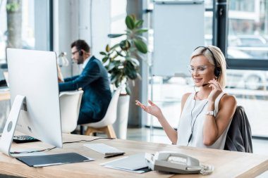 Selective focus of cheerful blonde woman in headset gesturing while talking near coworker stock vector