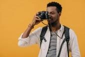 afroamerický muž pokrývající tvář s digitálním fotoaparátem izolovaným na oranžovém