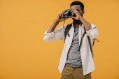 africká americká fotografka pokrývající tvář s digitálním fotoaparátem izolovaným na oranžovém