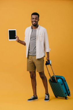 Cheerful african american man standing with luggage and holding digital tablet with blank screen on orange stock vector