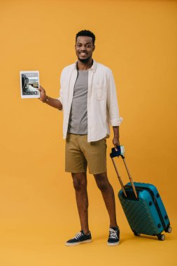 Cheerful african american man standing with luggage and holding digital tablet with tickets app on screen on orange stock vector