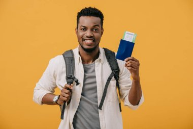 Happy african american man with backpack holding passport with air ticket isolated on orange stock vector