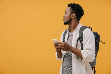 Handsome african american man with backpack holding smartphone isolated on orange stock vector
