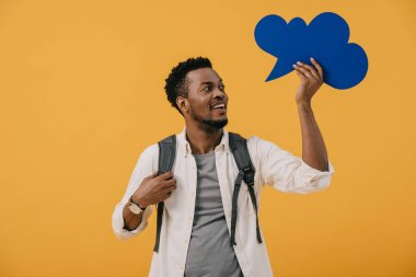 Cheerful african american man holding blue thought bubble isolated on orange stock vector