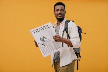Cheerful african american man standing with backpack and holding travel newspaper isolated on orange stock vector