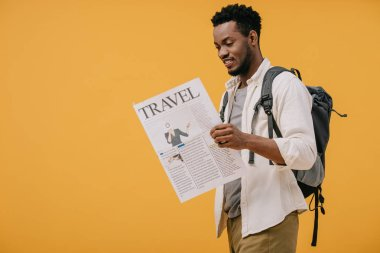 Cheerful african american man standing with backpack and reading travel newspaper isolated on orange stock vector