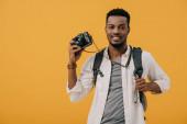 happy african american man holding digital camera isolated on orange