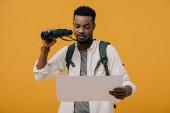 kudrnatý afroamerický muž držící dalekohled a dívá se na prázdný papír izolovaný na oranžovém