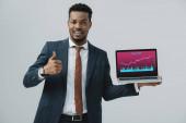 Veselý africký Američan muž držící notebook s obchodními analýzou na obrazovce a ukazující palec na šedou