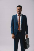 successful african american man standing with briefcase isolated on grey