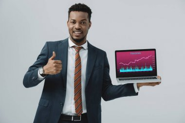 Cheerful african american man holding laptop with trading analyzing  on screen and showing thumb up isolated on grey stock vector