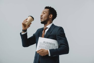 Handsome bearded african american man drinking coffee to go and holding business newspaper  isolated on grey stock vector