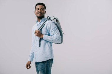 cheerful african american man standing with backpack isolated on grey