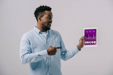 Happy african american man pointing with finger at digital tablet with medical app on screen isolated on grey stock vector