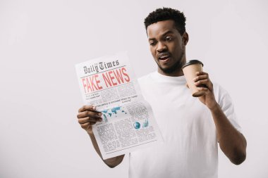 surprised african american man holding paper cup and reading newspaper with fake news lettering isolated on white