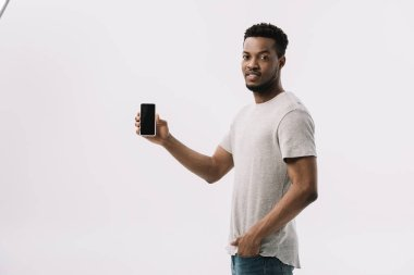Handsome african american man standing with hand in pocket and holding smartphone with blank screen on white stock vector