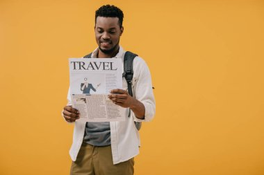 Happy african american man standing with backpack and reading travel newspaper isolated on yellow stock vector