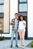 full length view of african american husband and wife showing thumbs up while standing near new house and looking at camera