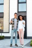 zobrazení plné délky afrického amerického manžela a manželky ukazující palce vzhůru, zatímco stojí u nového domu a dívá se na kameru