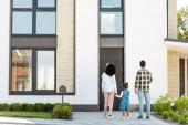 pohled na afroamerickou rodinu stojící poblíž nového domu, zatímco se rodiče drželi za ruce s dítětem