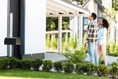 zobrazení plné délky afrického Američana a ženy, které se dívají na dům, zatímco stojí u trávníku