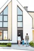 pohled na celou svou délku u africké rodiny stojící poblíž nového domu