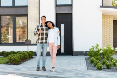 Full length view of african american husband and wife standing near new house and looking at camera while man showing thumb up stock vector