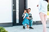 oříznutý pohled na ženu stojící blízko Afroameričana, zatímco otec objal dceru a držel klíč