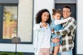 rodina stojící poblíž nového domu a dívá se na kameru, zatímco otec přidržující dítě a matku zobrazující klíč k fotoaparátu