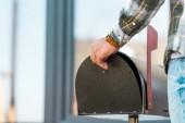 oříznutý pohled člověka otevření černé poštovní schránky blízko domu