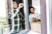 Afrikanisch-amerikanischer Mann öffnet Fenster, während Frau Schachtel öffnet
