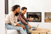 Fotografie Seitenansicht des Paares, das auf dem Sofa sitzt und auf den Laptop schaut, während der Mann Kreditkarte hält