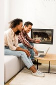 side view of african american man and woman sitting on sofa and looking at laptop while man holding credit card