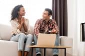 pohledný muž a Africká Američanka, kteří se dívali jeden na druhého a seděli na pohovce, zatímco manžel drží kreditní kartu