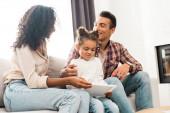 Kind spielt mit digitalem Tablet, während afrikanisch-amerikanische Eltern einander lächelnd anschauen