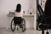 Rückansicht einer behinderten Geschäftsfrau, die im Rollstuhl am Arbeitsplatz sitzt