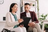 Schwerbehinderte Geschäftsfrau hält Klemmbrett neben aufmerksamen Geschäftspartner