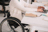 Photo cropped view of disabled businesswoman typing on laptop while sitting at workplace