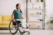 Lächelnde Behinderte, die zu Hause im Rollstuhl sitzt und wegschaut